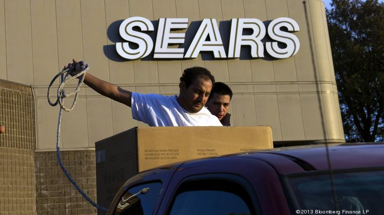 A U.S. flag flies as customers secure a new washing machine that was purchased at a Sears store in the back of a pickup truck.