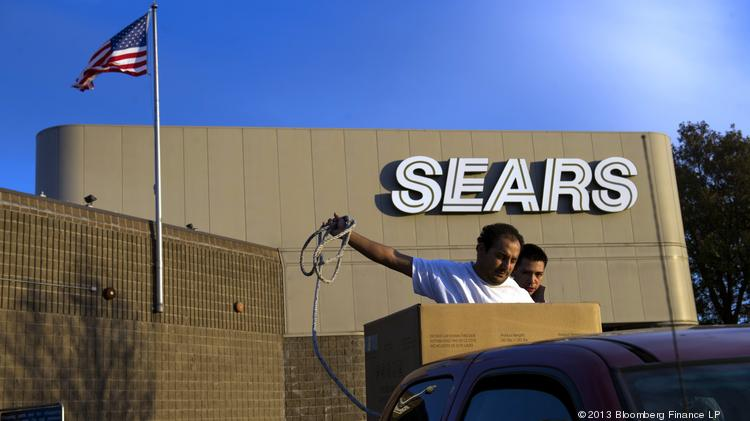 Customers secure a new washing machine that was purchased at a Sears Holdings Corp. store in the back of a pickup truck in Richmond, California.