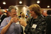 Gin Heroux clinks glasses with Cathy Campbell from The Centre for Women.