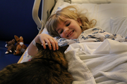 "Ruby Reese, who is 6, says she has two cats at home. She's happy to have a visit with Huck Finn, who popped into her room at Doernbecher Children's Hospital. ""He is so soft,"" she says, smiling."