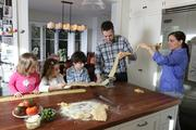 Making fresh pasta is a family affair with a hand cranked Atlas pasta machine. From left, Clementine, Lucy, William, Mark and Anne Marie Canlis work on making fresh pasta.
