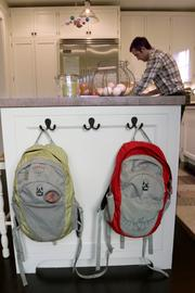 William and Lucy hang their backpacks on hooks on the island in the family's kitchen.