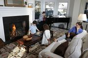 When the weather is cool enough, the Canlis family likes to build a fire in their living room fireplace at least once a week. From left, William and Lucy play chess, Mark plays piano with Clementine and Anne Marie relaxes. The grand piano used to be in his family's restaurant Canlis.