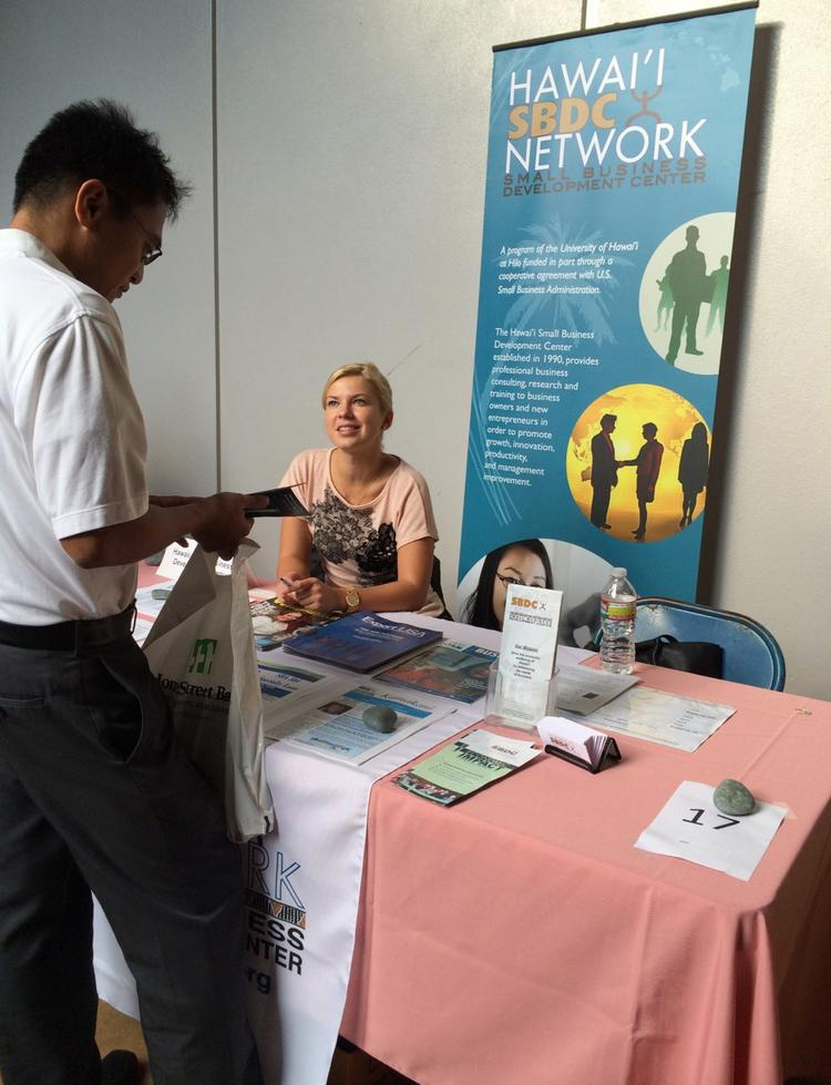 Viktorija Aniulyte of the Oahu Small Business Development Center speaks to an attendee of the Small Business Fair, which was held over the weekend at Leeward Community College.