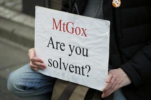 A Mt. Gox customer holds a placard while protesting outside a building housing the headquarters of Mt. Gox and its parent company Tibanne Co. in Tokyo, Japan, on Tuesday, February 25, 2014. Mt. Gox, the Bitcoin exchange that halted withdrawals this month, went offline as industry peers distanced themselves from the Tokyo-based company in an effort to defend the virtual currency.