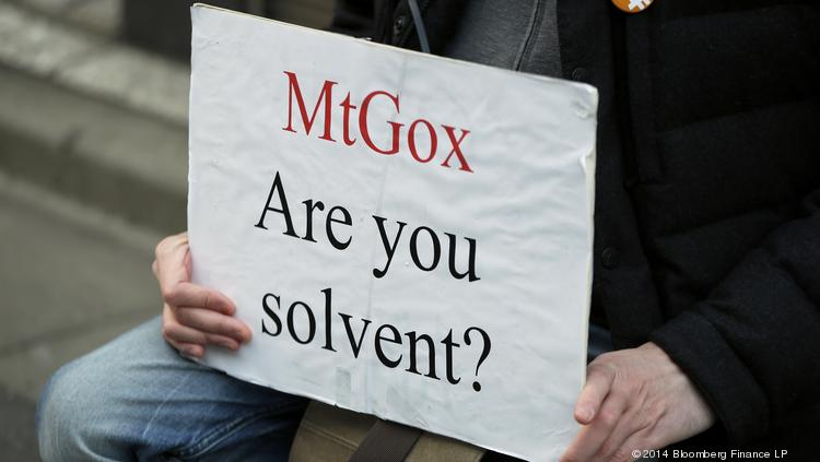 A Mt. Gox customer holds a placard while protesting outside a building housing the headquarters of Mt. Gox and its parent company Tibanne Co. in Tokyo. A California government agency warned consumers and investors about the dangers of bitcoin and other virtual currencies.