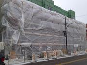 The other half of the project, shrouded in plastic to help keep work crews warm inside as they build out the interior.