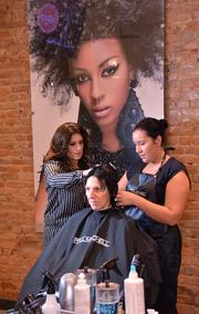 From left, learning leader Tamara Gizzi instructs student Jennifer Collins while she styles and cuts the hair of her mother, Cheryl Collins.