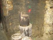 Sections of rotted wood pilings cut are piled up on the basement level.