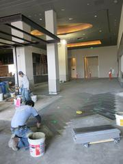 A worker lays new flooring at Apropoe's.