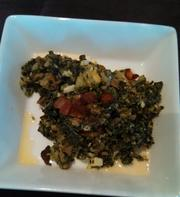 A chopped kale salad with tomato, hard-boiled egg, bacon crumbled blue cheese, mushrooms and corn.