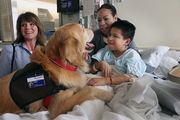 "Lorena Alvarez and her son Michael visit with Sara Hval and her golden retriever Oden at Providence St. Vincent Medical Center. ""You made his entire day,"" Alvarez said. ""You changed his whole mood."" Michael, who is 10, was waiting to hear if he might have to have his appendix out."