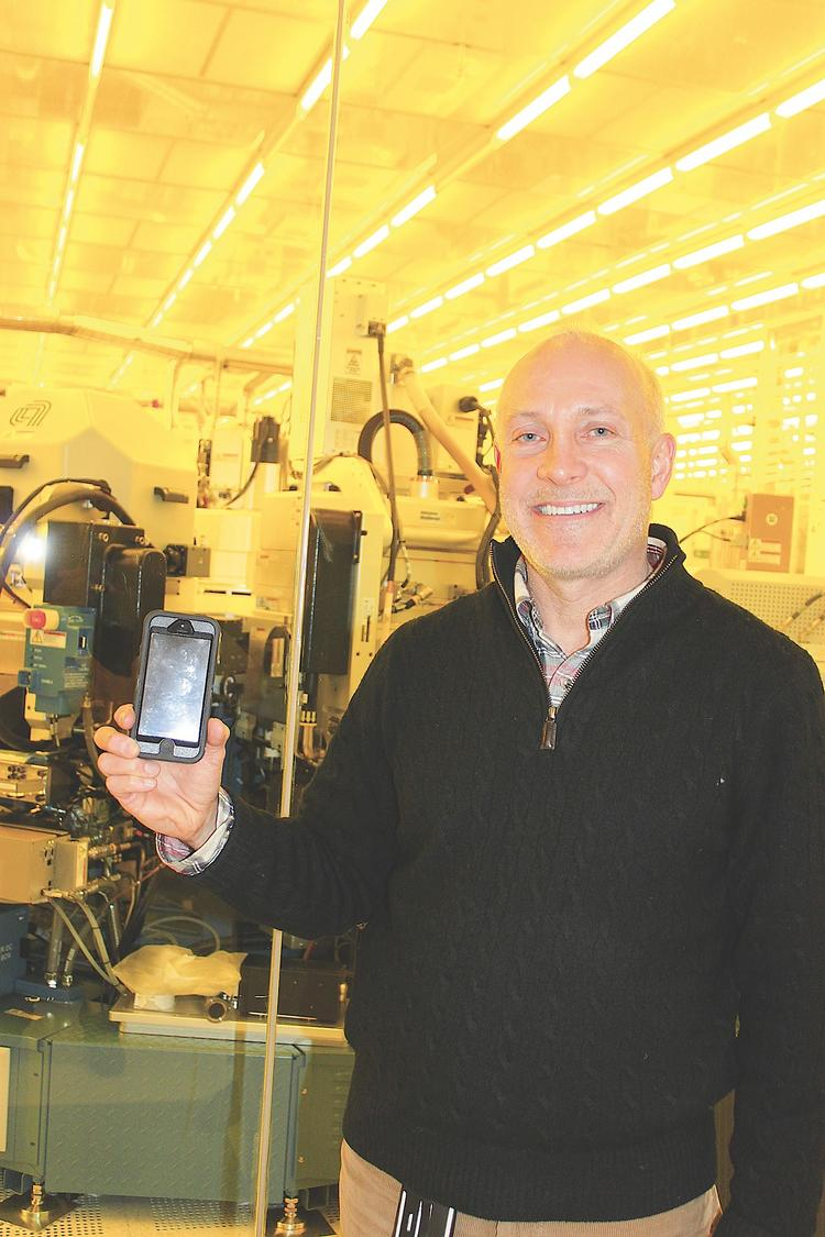 Michael Fancher, above, is vice president of the SUNY College of Nanoscale and Engineering. He holds a cell phone outside a clean room on the sprawling Albany campus where microchip technology aided the development of today's advanced phones. A typical cell phone has numerous chips whose roots can be traced to the educational and research center.