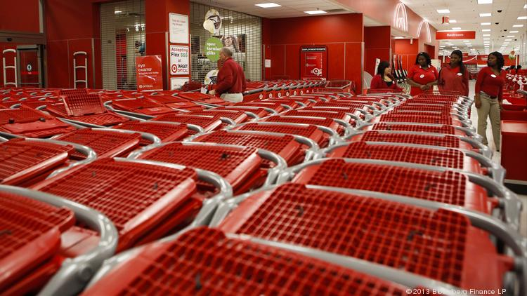 Employees arrange shopping carts in lines for customers at a Target Corp. store.