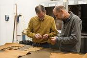 CCAD industrial and interior design Professor Joel Gundlach, right, inspects laser-cut material in the FabLab with his brother, Jim, who was a visiting artist this semester.