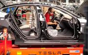 An employee works on a Telsa Motor Inc. Model S sedan as it makes its way along an assembly line.