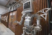 """A Specialized industrial designer took on an art project in early 2014, emblazoning the company's """"innovate or die"""" slogan on a gate that cordons off pre-market products. The adjacent robot is just for fun."""