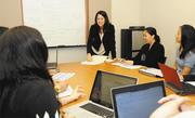 Kanoe Naone, CEO of INPEACE, standing, works with her grant-writing team at their Kapolei office.