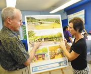 Terry George, executive director and vice president of the Harold K.L. Castle Foundation, and Maureen Purington, clubhouse director for the Boys and Girls Club, look over renderings for the club's expansion at Kailua Intermediate School. The $10 million project will break ground next month.