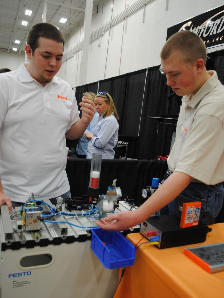 """Apprenticeship 2000 students at Blum Inc., Jacob Mountz, left, and Micah Stockfish, help out at the Career Expo in Lincoln County, a part of """"Manufacturing, A Future that Works."""""""