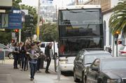 Google Inc. responded to protests over its commuter buses using downtown stops by sponsoring a $6.8 million program to give low-income San Francisco kids free Muni passes. Photographer: David Paul Morris/Bloomberg