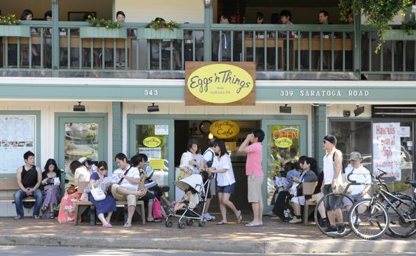 Spending by visitors to Hawaii declined for the sixth straight month in January. Seen here in this file photo are tourists outside the popular Eggs 'n Things restaurant in Waikiki.