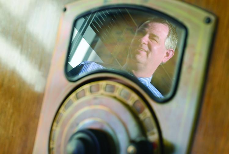 Jon McTaggart, president and CEO at American Public Media, reflected in a radio at APM's offices.