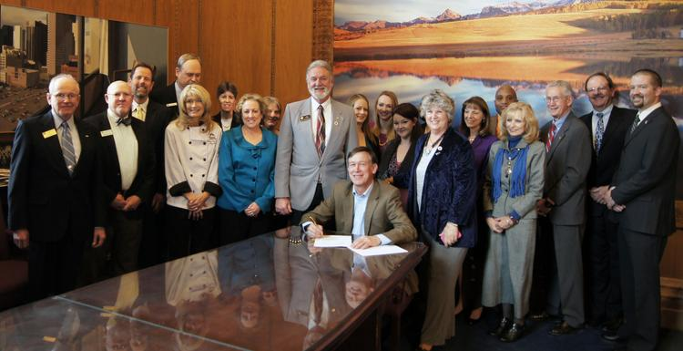 Colorado Gov. John Hickenlooper signs SB 4 Thursday. Behind him are bill sponsors and supporters, including Colorado Community College System Nancy McCallin, state Rep. Jim Wilson and state Sen. Nancy Todd.