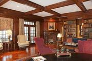 The study features exposes wood beams and built-in bookcases.