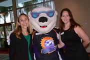 Orlando Solar Bears mascot Shades takes time for a photo with Orlando Business Journal's Mary Dominguez and Jennifer Janelle.
