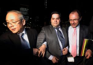Mark Karpeles, chief executive officer of Mt. Gox, center, is escorted as he leaves the Tokyo District Court in Tokyo, Japan, on Friday, Feb. 28, 2014. Mt. Gox, once the world's largest Bitcoin exchange, filed for bankruptcy in Japan, focusing attention on the digital currency's risks. Photographer: Tomohiro Ohsumi/Bloomberg *** Local Caption *** Mark Karpeles