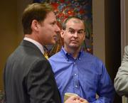 William McGuire of exp listens as Peter Vilmos of Burr & Forman LLP speaks with a group during the networking session.