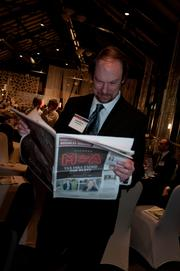 Polaris' Steve Smith reads the Minneapolis/St. Paul Business Journal at the Executive of the Year dinner.