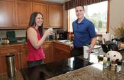 Camille Adair (left) and Jesse Hatch relax in their new kitchen. The couple not only offered $6,000 more than the asking price, but wrote a letter to the sellers describing their plans to raise a family in the home.