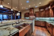 The kitchen features custom woodwork and granite countertops.