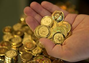 Mike Caldwell, of Casascius, displays a handful of Bitcoins that were just made for a photograph in Sandy, Utah, U.S., on Friday, April 12, 2013. These coins, which have become a symbol for the digital currency are no longer being produced.