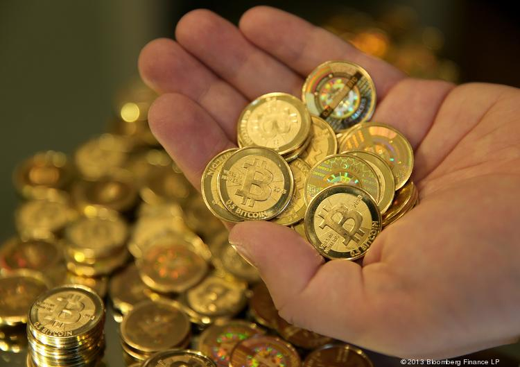 Mike Caldwell, of Casascius, displays a handful of Bitcoins that were just made for a photograph in Sandy, Utah, U.S., on Friday, April 12, 2013.