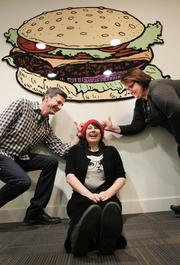 Cheezburger executives (from left) Kenny Stocker, executive director, Heather Bradley, creative director, and Mary Lewis, director of marketing and public relations, goof around in the lobby of their Queen Anne offices in Seattle.
