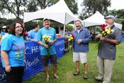 From left, the Hawaii Pacific Health executive team, Gail Lerch, Art Gladstone, David Okabe and John LaForgia preparing to give each finisher a rose after the Hawaii Pacific Health Women's 10K run at Kapiolani Park in Honolulu.