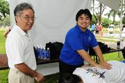 Stephen Sasaki, instructor for Kapiolani Community College's massage therapy program, and student Casey Fukuda volunteering massage services at the Hawaii Pacific Health Women's 10K at Kapiolani Park in Honolulu.