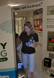 Shani Magosky, franchise owner for h.u.m.a.n. fills the machine with water bottles.
