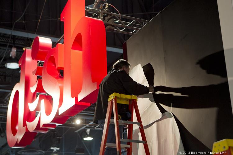 A worker installs a display at the Dish Network booth during the 2013 Consumer Electronics Show in Las Vegas on Jan. 8, 2013.