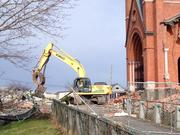 Workers from Dan's Hauling & Demolition in East Greenbush carefully remove one of two plaques from the church portico to prepare for the razing. The plaques will be given to the Roman Catholic Diocese of Albany.