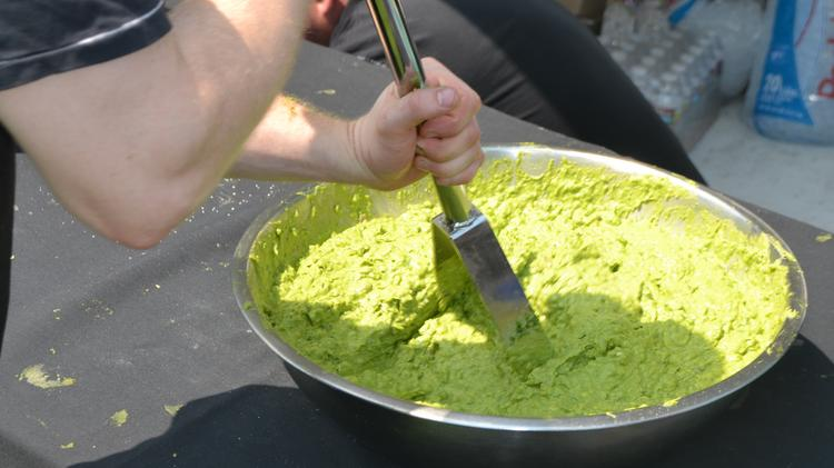 A Chipotle employee makes guacamole at the Chipotle Cultivate Festival in Denver in August 2013.