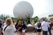 Guests pose by a topiary scene featuring Disney characters on a butterfly hunt.