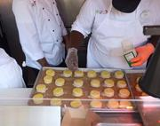 Inside the kitchen, chefs prepare the biscuits for the oven.