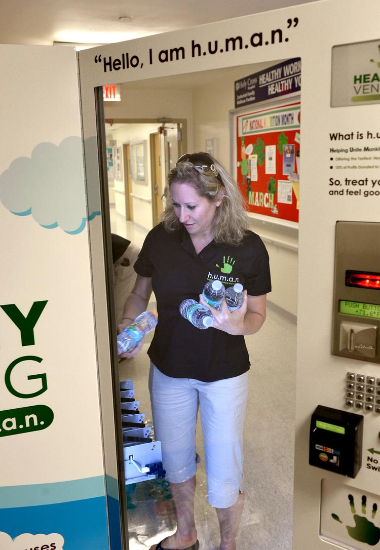 Shani Magosky fills a vending machine at Fort Lauderdale's Holy Cross Hospital with bottled water.