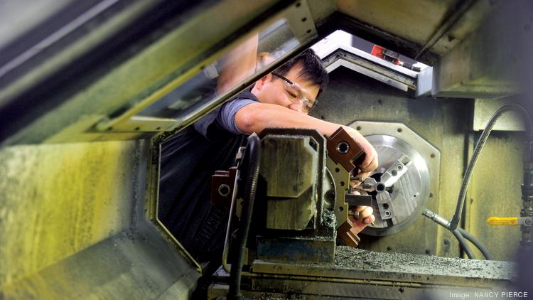A Poly-Tech Industries lathe operator prepares to make bearings in the company's Huntersville plant.