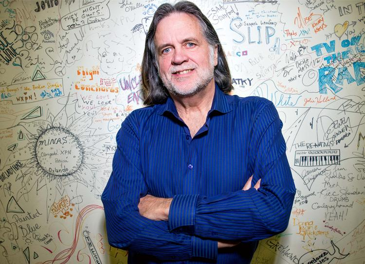 Roger LaMay, general manager of WXPN, in front of a wall signed by artists.