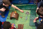 An overhead view of kids playing with Harvard's bio-inspired robots – and some plastic bugs, too.
